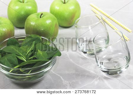 Bowl With Fresh Spinach Leaves, Apples, Empty Glasses And Straws. Concept Of Helathy Preparation Of