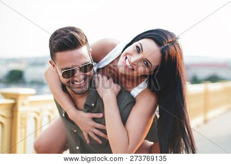 Happy Young Caucasian Urban Couple Doing Piggyback And Toothy Smiling At Outdoors, Happiness