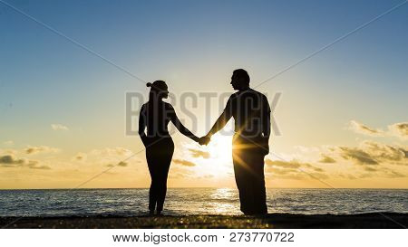 Young Couple Is Walking In The Water On Summer Beach. Sunset Over The Sea.two Silhouettes Against Th