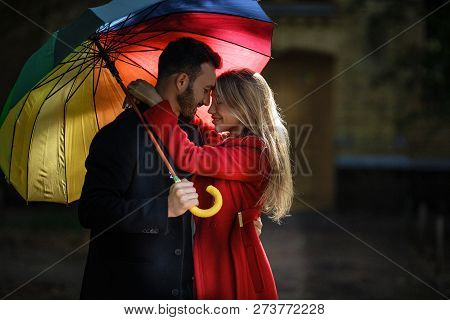 Beautiful Couple Hugging Outside And Standing Under Colorful Umbrella. Love Story Concept.