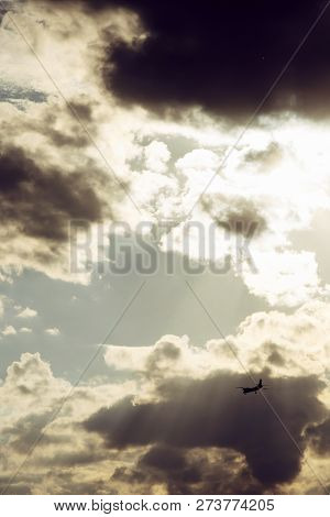 Silhouette of passenger airplane in backlight on background of cloudy sky with sun rays. Atmospheric background with passenger flight and sunlight through clouds. Air tourism. poster