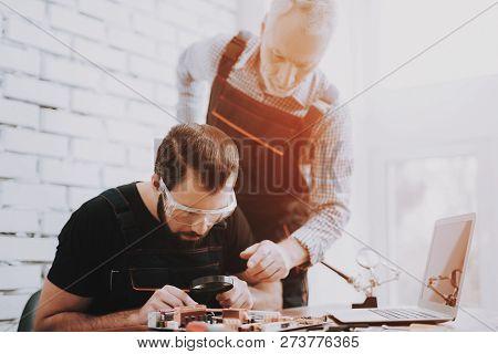 Two Men Repairing Hardware Equipment In Workshop. Repair Shop. Worker With Tools. Computer Hardware.