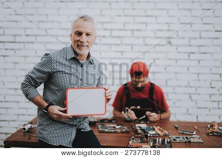 Worker Giving To Man Fixed Laptop In Workshop. Worker With Tools. Computer Hardware. Young And Old W