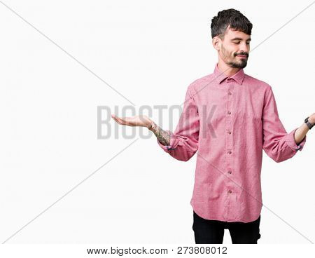 Young handsome man wearing pink shirt over isolated background Smiling showing both hands open palms, presenting and advertising comparison and balance