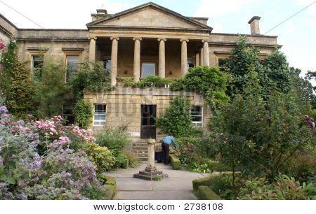 Decorative Facade With Pediment And Columns. Sunclock In Garden.