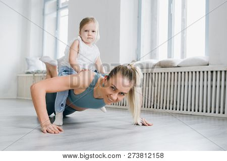 Mother And Baby Girl Do Exercises Together In The Gym