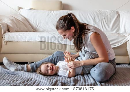 Cute Small Boy With Down Syndrome Playing With Mother In Home Living Room