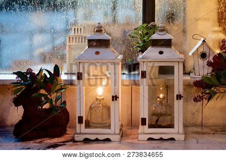 Christmas Decoration With Candle Wooden Lantern, Bird Home And Plants Against Frosty Window On Dusk