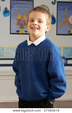 Portrait Of Male Primary School Pupil Standing In Classroom