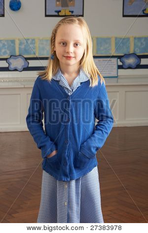 Portrait Of Female Primary School Pupil Standing In Classroom