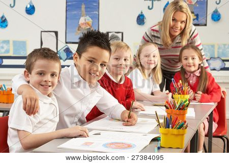 Group Of Primary Schoolchildren And Teacher Working At Desks In Classroom