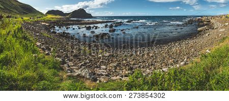 Panoramic view of Northern Ireland bay. Stunning shoreline surrounded by the boulders. Grass covered land under the blue cloudy sky. Wild nature environment. Overwhelming Irish landscape.