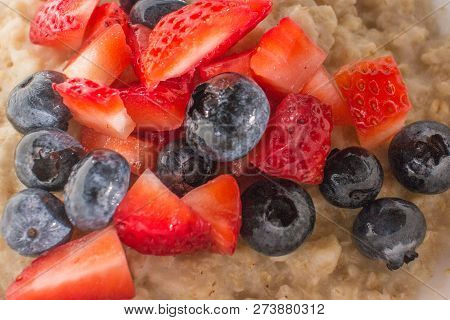 Blueberries & Strawberries On Top Of Oatmeal In A White Bowl.