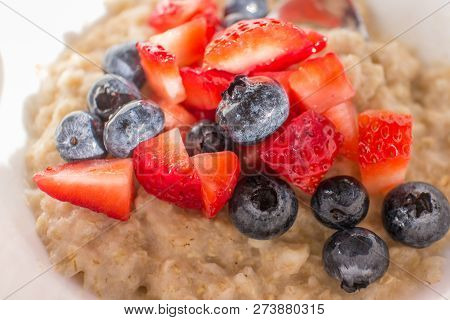 Blueberries & Strawberries On Top Of Oatmeal In A White Bowl With A Spoon.