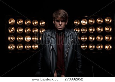 Young Stylish Man In Leather Cool Black Jacket In Red Golf In Stylish Trousers, Posing In A Dark Stu