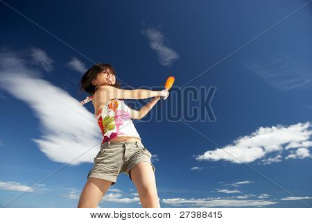 Teenage girl playing baseball on beach