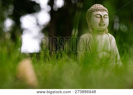 Small White Buddha Statue In A Meditation Pose With Green Grass Foreground And On Natural Bright Blu