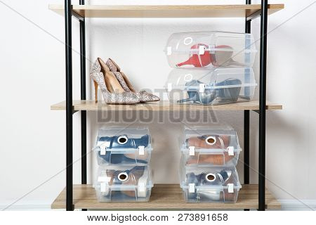 Footwear And Plastic Boxes On Shelves Near Wall. Shoe Storage Organization