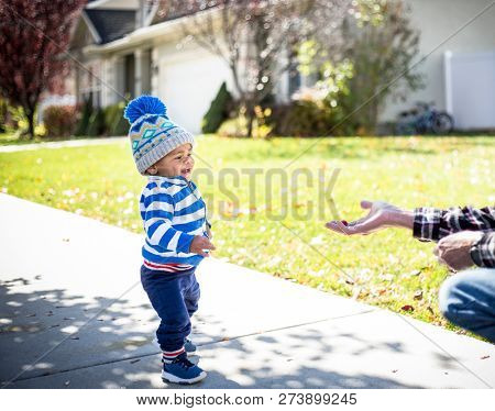 Cute smiling little boy walking towards an outstretched hand with a free handout of food or a treat. trying to get a delicious treat. Concept photo for giving poster