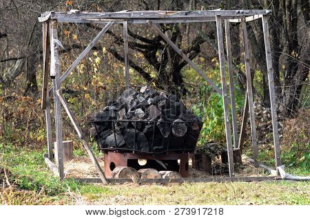 A pile of stones and wooden frame of the bathhouse for tourists in the wild forest near the river, autumn. poster