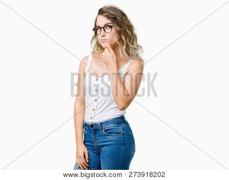 Beautiful young blonde woman wearing glasses over isolated background with hand on chin thinking about question, pensive expression. Smiling with thoughtful face. Doubt concept.