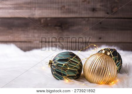 Bright Green And Golden Balls On White Fur Background Near By Vintage Wooden  Wall. Decorative Chris