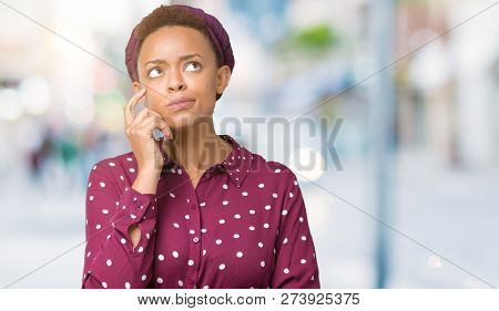 Beautiful young african american woman wearing head scarf over isolated background with hand on chin thinking about question, pensive expression. Smiling with thoughtful face. Doubt concept.