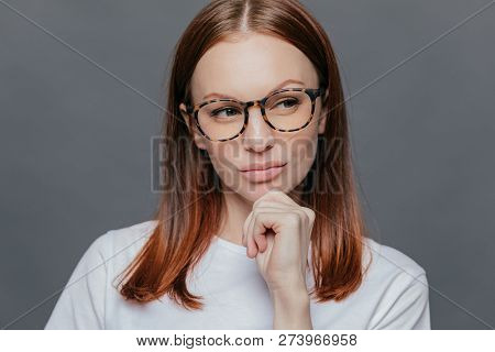 Thoughtful Caucasian Woman With Full Lips, Dark Brown Hair, Looks Thoughtfully Aside, Dressed In Whi