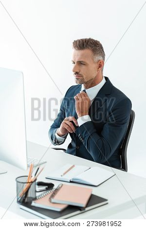 Handsome Businessman Tying Tie At Table With Computer Isolated On White