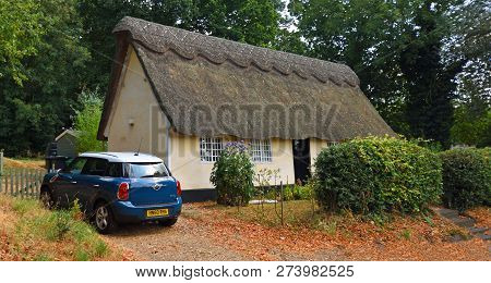 Old Warden, Bedfordshire, England - July 25, 2018:  Traditional Thatched Cottage With Mini Motor Car