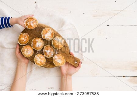 Top View On Womans Hands Holding Wooden Board With Homemade Muffins And Childs Hand Taking On Muffin