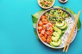 Tasty appetizing poke bowl served with salmon, avocado, rice, salad with edamame. Blue background. View from above. Horizontal. poster