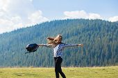 Success concept. Hiker woman cheering elated and blissful with arms raised in sky after hiking to mountain top poster