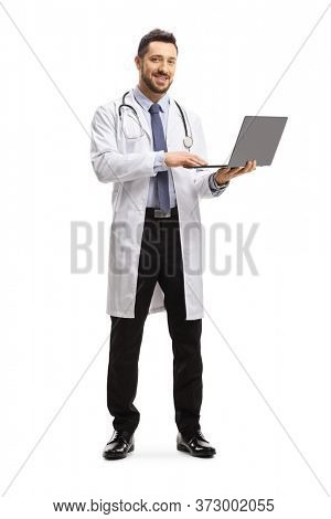 Full length portrait of a male doctor standing and using a laptop computer isolated on white background