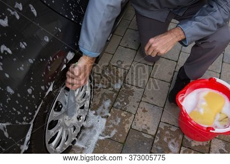 Male auto service staff washing a tyre with brush