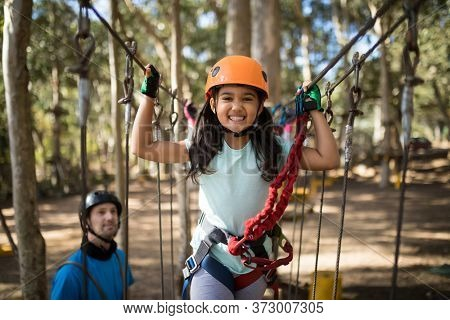 Portrait of cute girl crossing zip line on a sunny day