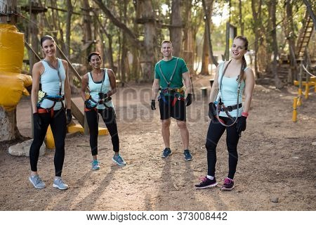 Portrait of happy coach and trainee standing in forest