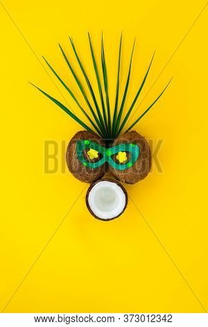 Funny Face With Astonished Expression Made Of Coconuts And Pallm Leaf On Yellow Background. Flowers