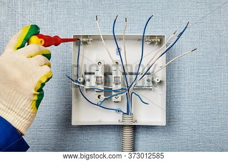 Installation Of A Switchboard Or Consumer Unit. An Electrician Secures A Copper Wire To A Neutral Ba