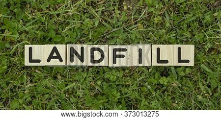 The Word Landfill Is Written The Wooden Blocks On A Background Of Grass. The View From The Top. Envi