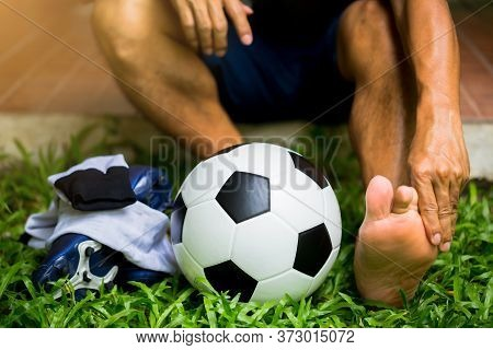 Soccer Ball And Sport Shoes On Green Grass With Soccer Player Catch The Ankle Of The Feet Because Of