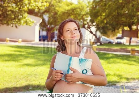 An Expectant Mother With A Tummy With A Book Reading Stories And Daydreaming Looking Up To The Side