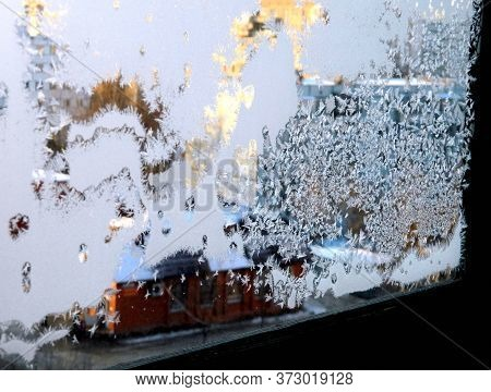 The Patterns Made By The Frost On The Window. A Pattern Of Dog-shaped In-shape On A Glass Made By Fr