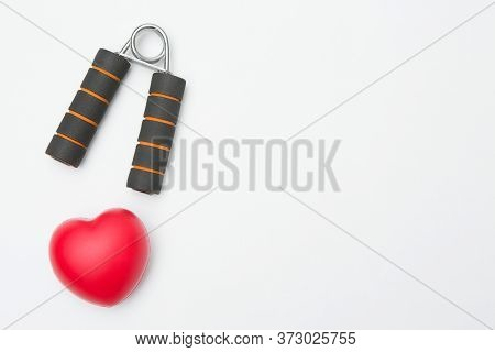 Hand Grip And Heart Shaped Squeeze Ball For Hand Muscle Exercise On White Background And Copy Space