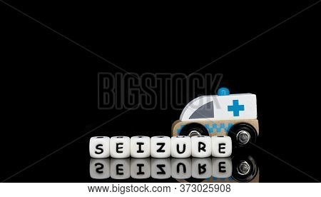 Alphabet Letters Spelling A Word Seizure With A Model Ambulance In The Background. Medical Emergency