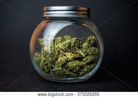Medical Marijuana Flower Buds In Glass Jar On Dark Backdrop