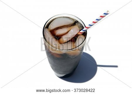 Cola Flavored Soda Pop. Cola Soda Pop with Ice in a Glass Tumbler. Isolated on white. Room for text. Cola flavored soda is enjoyed world wide.
