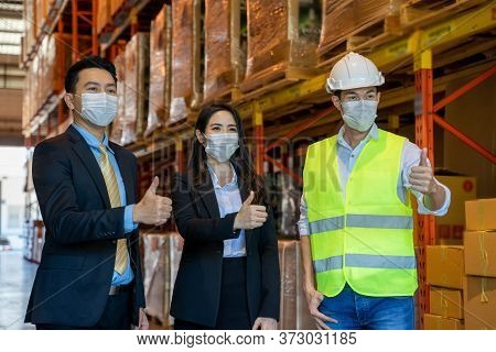 Business People With Warehouse Workers Wearing Hard Hats Standing In Aisle Between Tall Racks With P