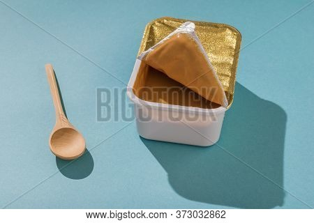 Wooden Spoon With An Open Plastic Container With Peanut Paste. Natural Peanut Cream.