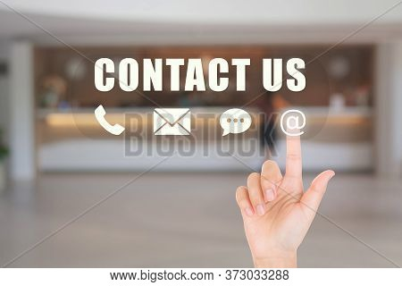 Call Center And Contact Us Concept : Hand Choosing And Pressing On Contact Us Icon Symbols With Blur